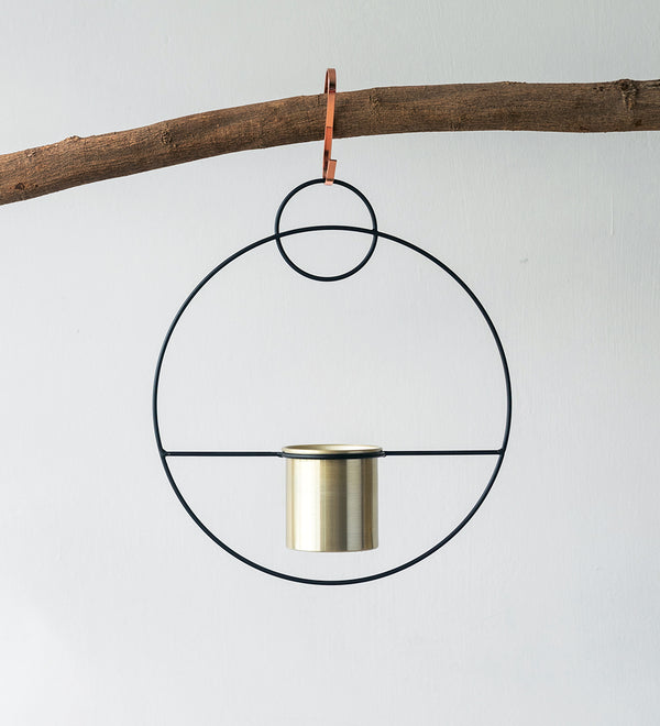 Beautiful hanging black and gold ring design planter hanging from wooden branch