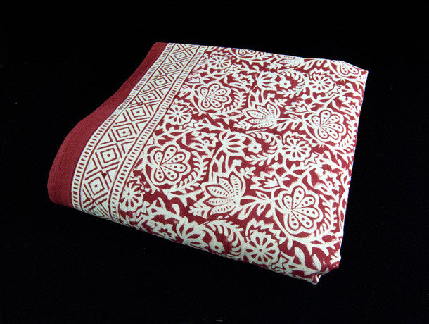 Red block printed organic cotton tablecloth featuring natural dyes and a bold white and red floral and geometric pattern