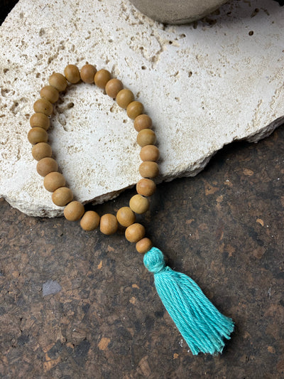29-bead wrist mala made from genuine sandalwood beads with turquoise blue cotton tassel. On elastic. This is a large mala bracelet