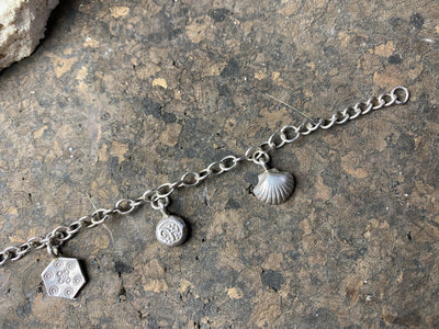 Sterling silver charm bracelet with 6 charms including elephant, dragonfly and seashell, with plenty of room to add more charms. With extension chain