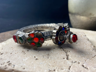 Very high grade silver, women's hinged cuff from Afghanistan. Hollow construction with a hexagon profile, this bracelet is hinged and features several florets of silver set with glass stones in red, blue and green, and a high profile reverse screw fastening and two stylised half opium poppies. 19th century