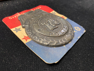 pressed tin novelty kid's police badge is still mounted on its original red white and blue display card. Made in Japan circa 1950