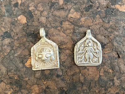 Antique silver amulets representing the Hindu god Shiva, traditionally worn for protection and good luck. Originating in southern India and dating from the late 19th century.