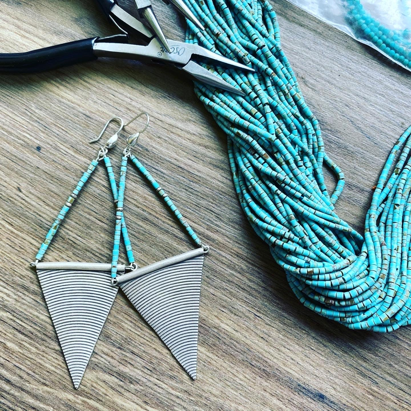 "Tribal silver and turquoise earrings with a difference. Handmade 95% pure silver and natural Arizona turquoise with tiny ""eye bead "" tribal silver bead detailing. These are big earrings - at over 10 cm in length they hang almost to the shoulder - but they're light and easy to wear."