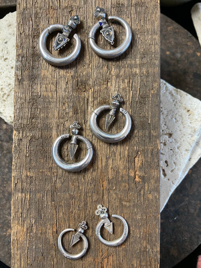 Three pairs of tribal silver earrings called Bent Arrow. Worn pushed sideways through the ear by Yao women. High grade silver, they can only be worn with an extended piercing