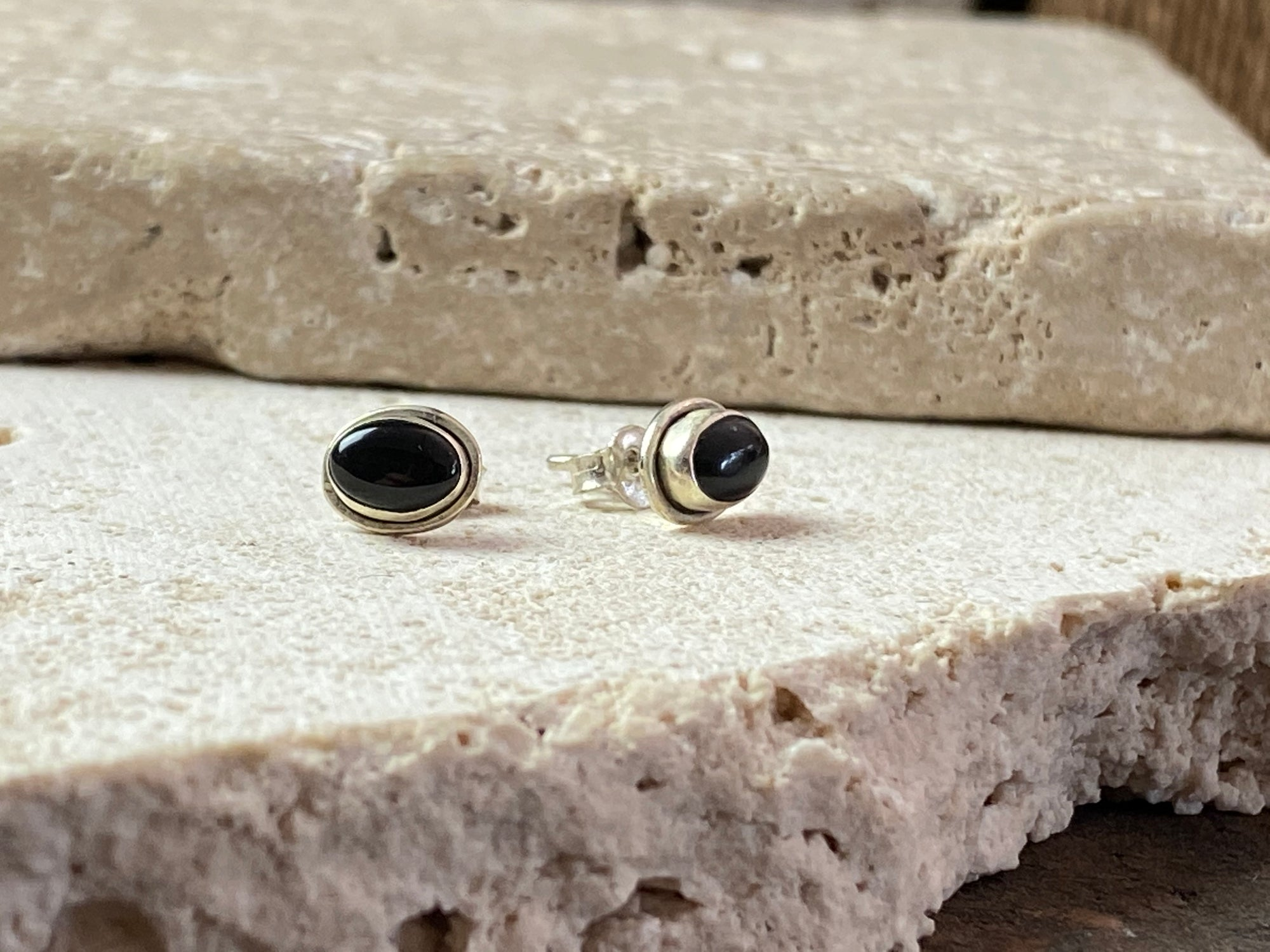 Simple black onyx and sterling silver ear studs with a simple raised bezel setting