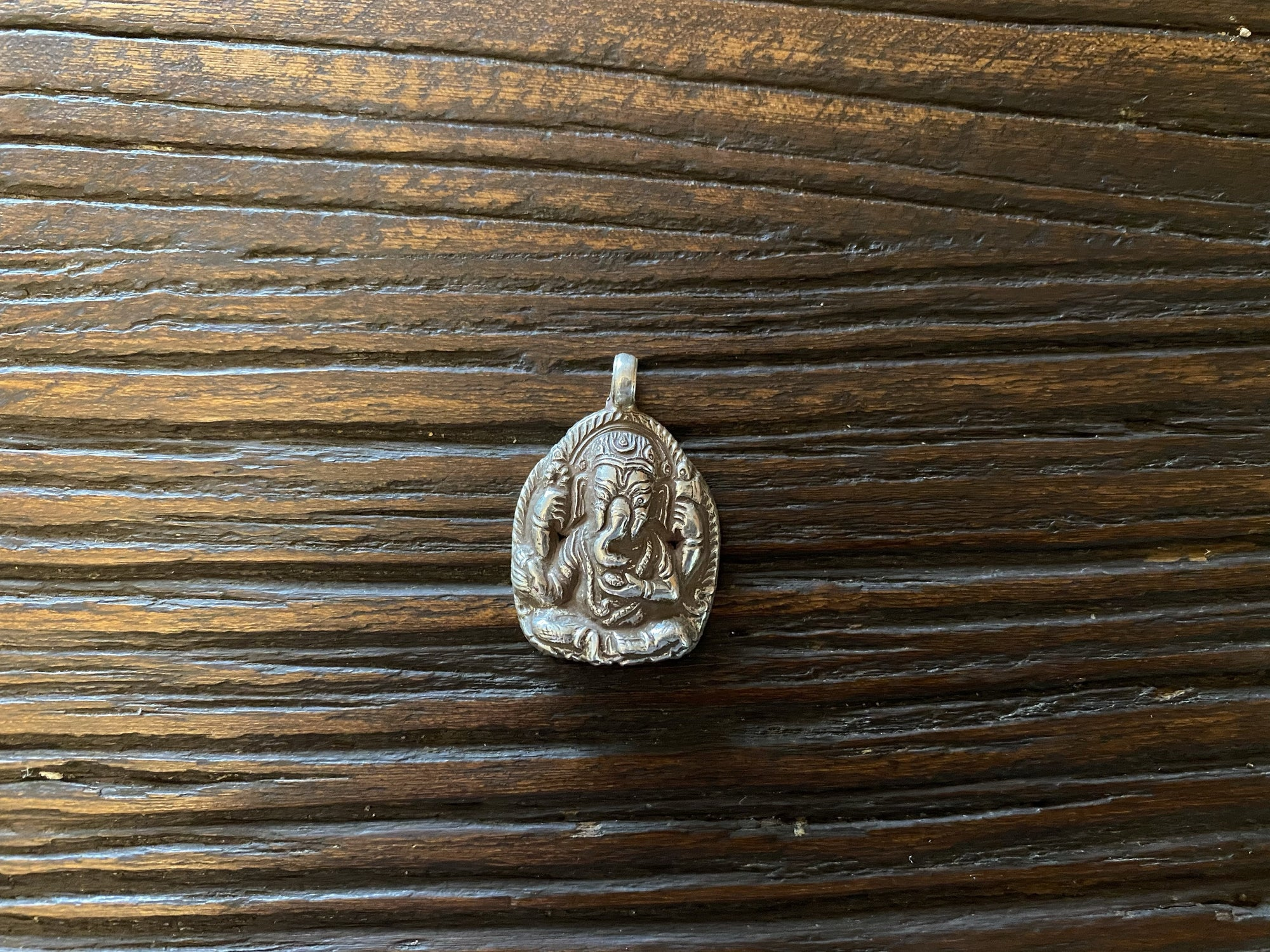 Hollow cast, high relief silver pendant featuring Lord Ganesha. The back of the pendant holds the Buddhist mantra Om Mani Padme Hum.  Sterling silver, from Nepal