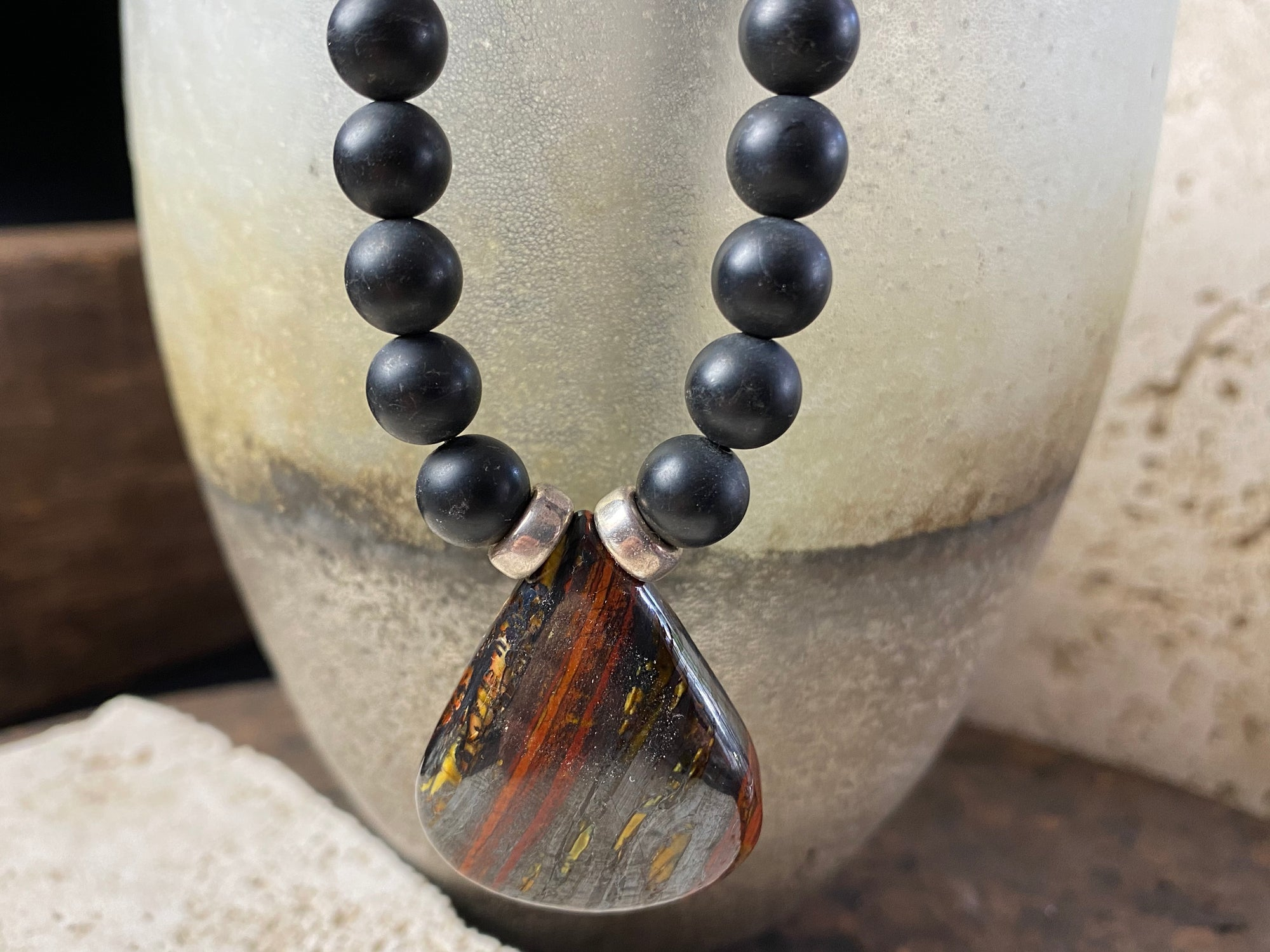unique necklace of unpolished matte black onyx beads with a teardrop pendant of red tigers eye. Sterling silver clasp and detailing