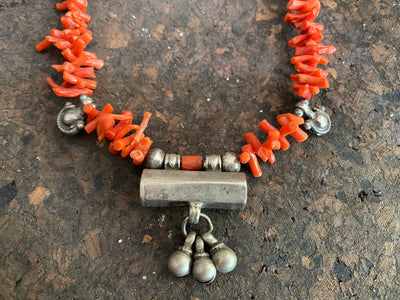 Natural red Mediterranean coral with a belled silver Afghani amulet and small silver pendants