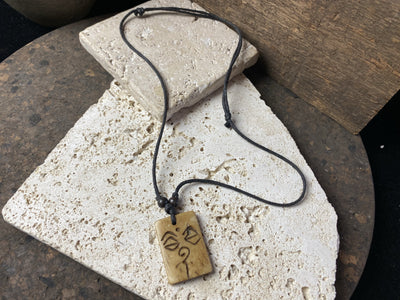 Bone pendant carved with the eyes of buddha on an adjustable string cord