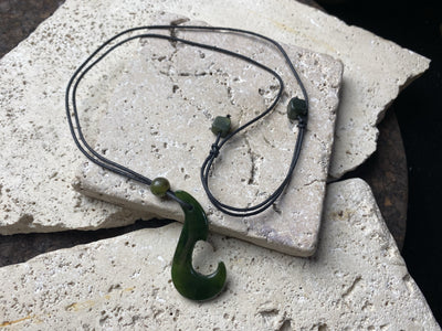 Natural green jade hei matau fish hook pendant, hand carved in New Zealand by a Maori craftsman.