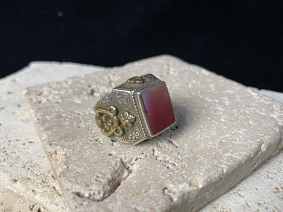 Men's signet ring from Turkmenistan,  high grade silver  set with a clear red carnelian stone, covered in scroll work detailing, highlighted with raised brass work embellishments that are indistinguishable from gold