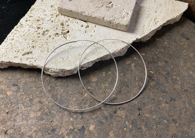 Simple, slender mid size silver hoop earrings. Sterling silver, with a simple inline hinged fastener that looks completely seamless