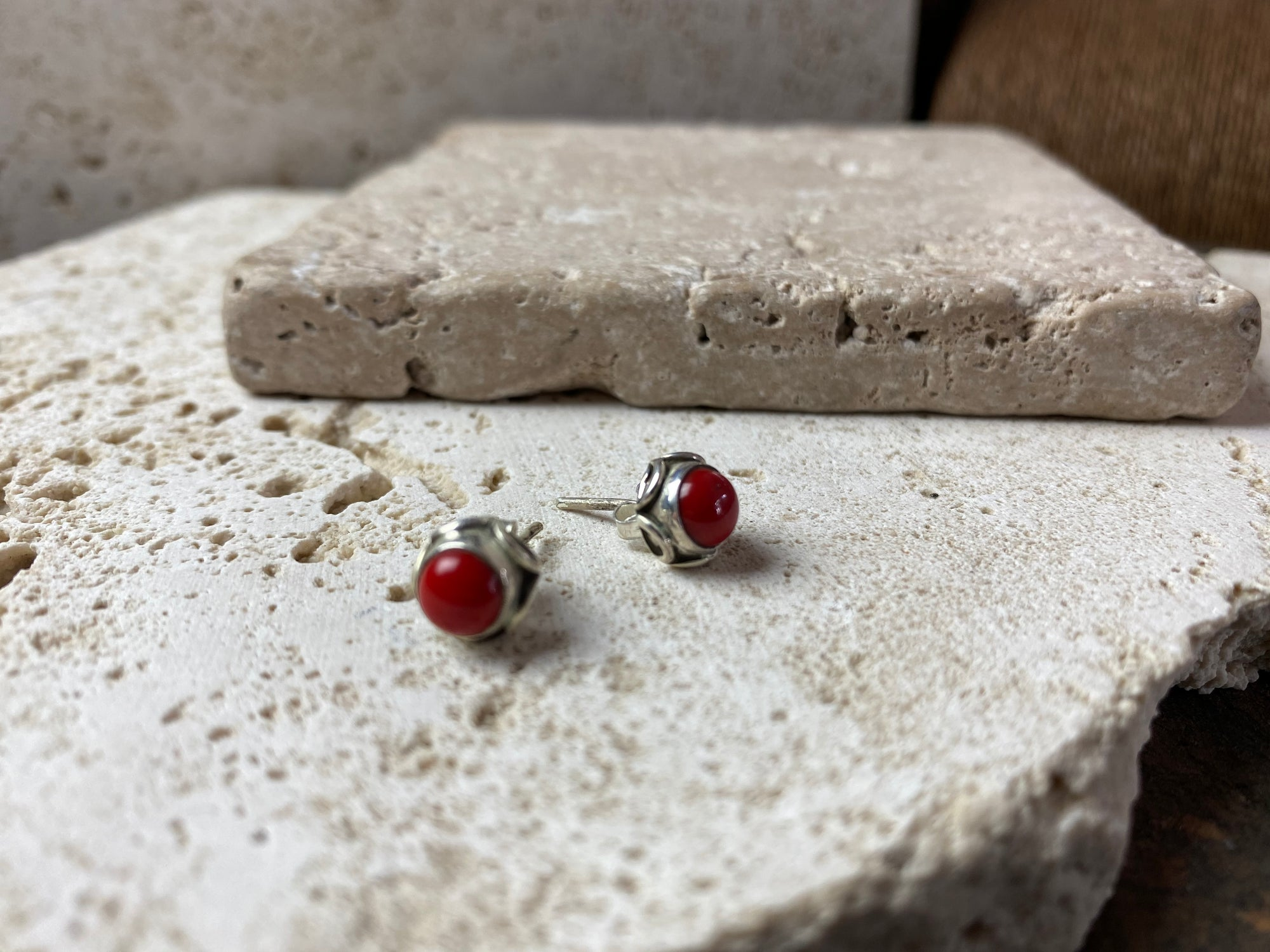 large coral and silver stud earrings featuring a patterned silver bezel