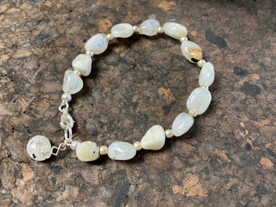 "Boho style bracelet made from natural rainbow moonstone stones, finished with sterling silver. A single moonstone drop acts as both a feature to catch the eye and as a counterweight, keeping the bracelet sitting the right way up on the wrist.  18.5 cm length (7.3"")"