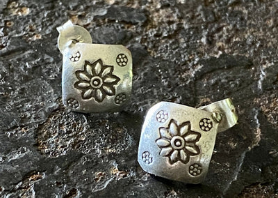Silver stud earrings in a diamond shape with flower patter. Post and stud back
