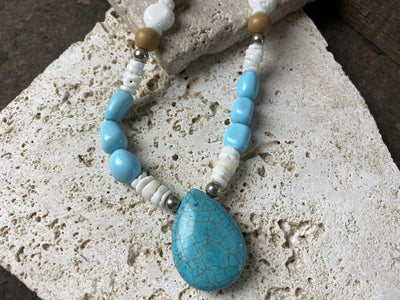 A casual beach vibe necklace in shades of blue and white, made with composite turquoise, blue stone, heishi shell, white coral and sandalwood beads