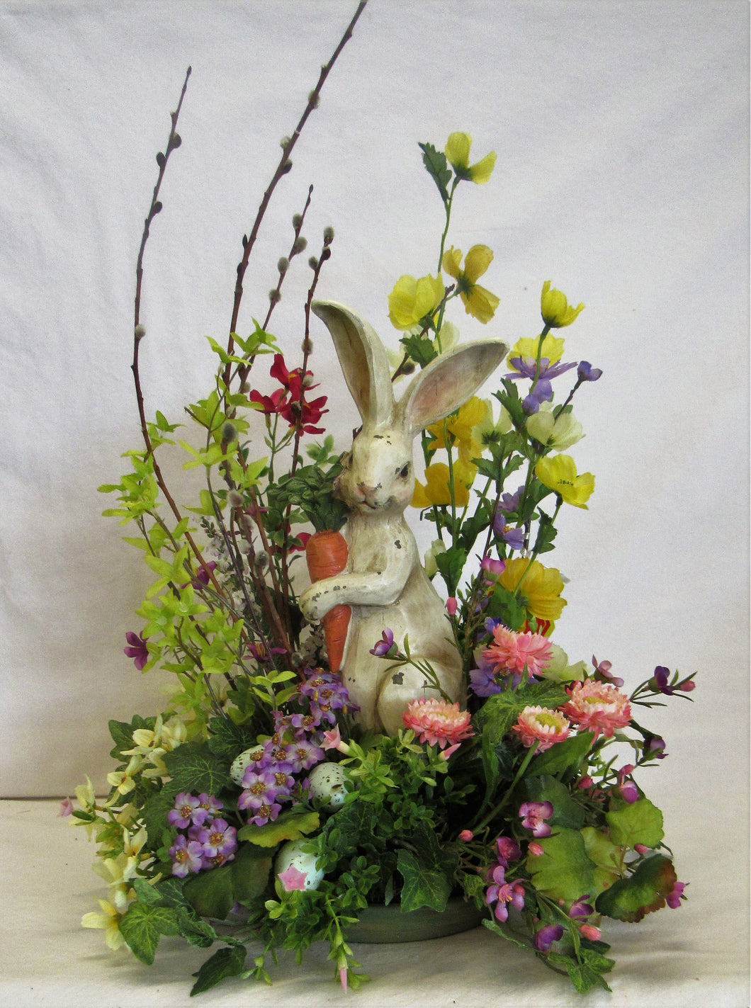 Easter Floral Arrangement with Ceramic Bunny, Purple, Yellow and Pink Florals, and Mini Easter Eggs - April's Garden Wreath