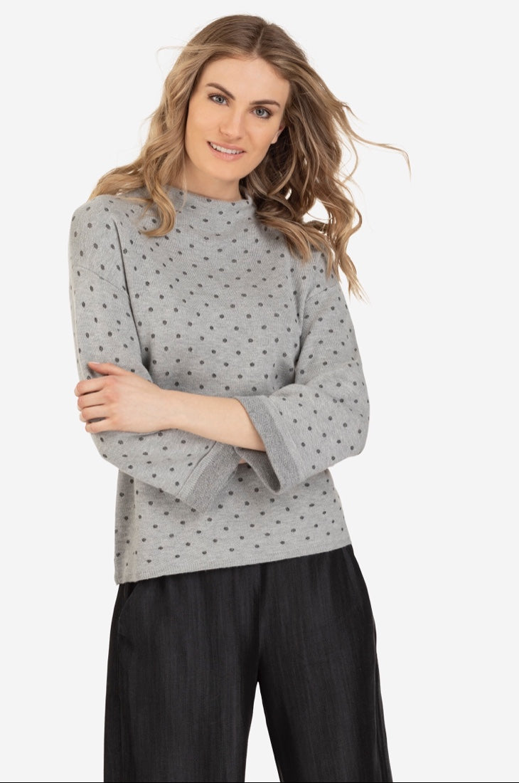 Canadian Designed Grey on Grey Polka dot Print Funnel neck style sweater with a rolled sleeve. Pair this top with a cute denim and wedge boot or fabulous dress pant. Shop deserve jewels