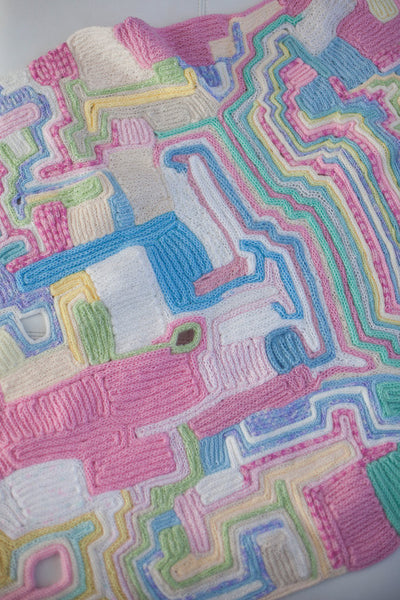 baby cot blanket made of recycled wool scraps. All pastel colors. Looks like the land from above