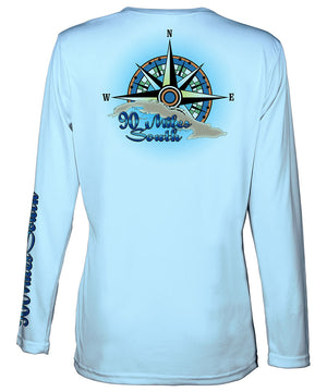 Ladies Cuban t-shirt | back view of a light blue long sleeve performance v-neck t-shirt depicting a blue green compass rose artwork and outline of the island of Cuba