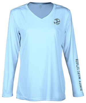 "front view of a ladies light blue v-neck performance shirt with 90 Miles South Round left chest logo and right sleeve copy saying ""90 Miles South"""