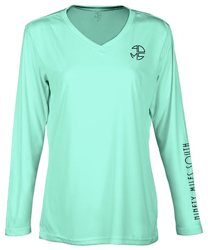 "front view of a ladies sea foam green v-neck performance shirt with 90 Miles South Round left chest logo and right sleeve copy saying ""90 Miles South"""