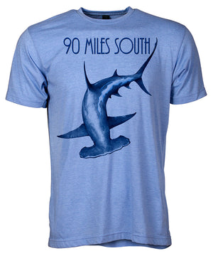 Front view of short sleeve heather blue tee shirt with dark blue artwork of 90 Miles South Hammerhead Shark
