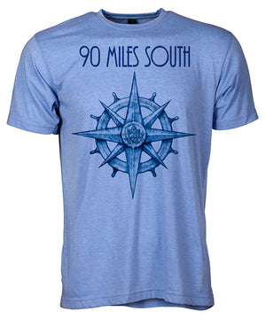 Front view of short sleeve heather blue tee shirt with dark blue artwork of 90 Miles South compass