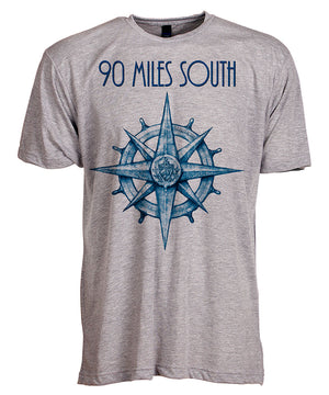 Front view of short sleeve heather grey tee shirt with blue artwork of 90 Miles South compass