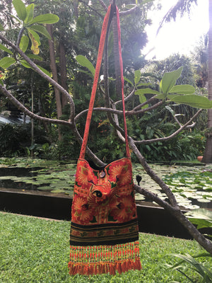 Ngam Upcycled Orange Multi Color Printed Festival Crossbody with Hand Beaded Detail and Mini Yarn Tassel Lifestyle