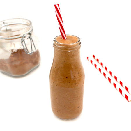 In the center of the image is a clear milk-style bottle filled with VegAnnie's Skinny Mocha Frappuccino, which is sugar-free and keto friendly. Another bottle to the left has a powdered version of the sugar-free frappuccino.