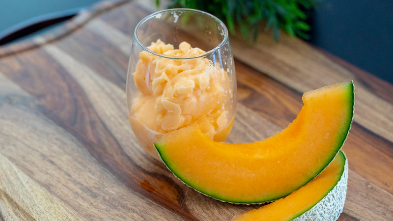 Two cantaloupe are placed next to a clear cup filled with light orange cantaloupe slushy.