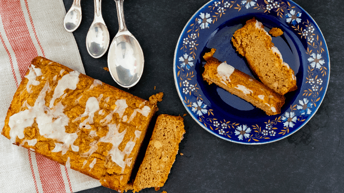 A loaf of low carb pumpkin bread is displayed on a dark tabletop in the bottom left corner. A piece is sliced off and lays in where it fell. The loaf is drizzled with white frosting. Two other pieces are on a blue, flowered plate in the top right corner.