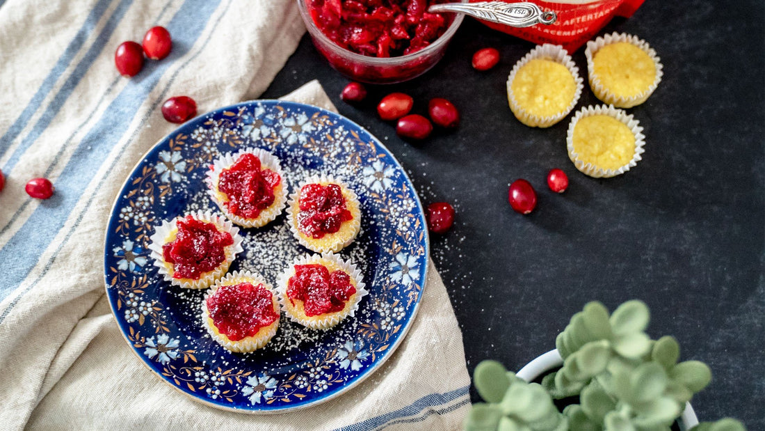 A blue plate with white and brown flowers sits on a white with blue lines dish towel. Cranberries, cupcakes, and Lakanto sweetener are scattered around the table.