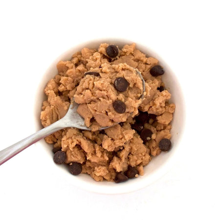 A spoonful of sugar free chocolate chip cookie dough is held above a white bowl filled with sugar free chocolate chip cookie dough. The recipe is from VegAnnie. VegAnnie and Lakanto work to provide healthy sugar-free recipes to everyone.