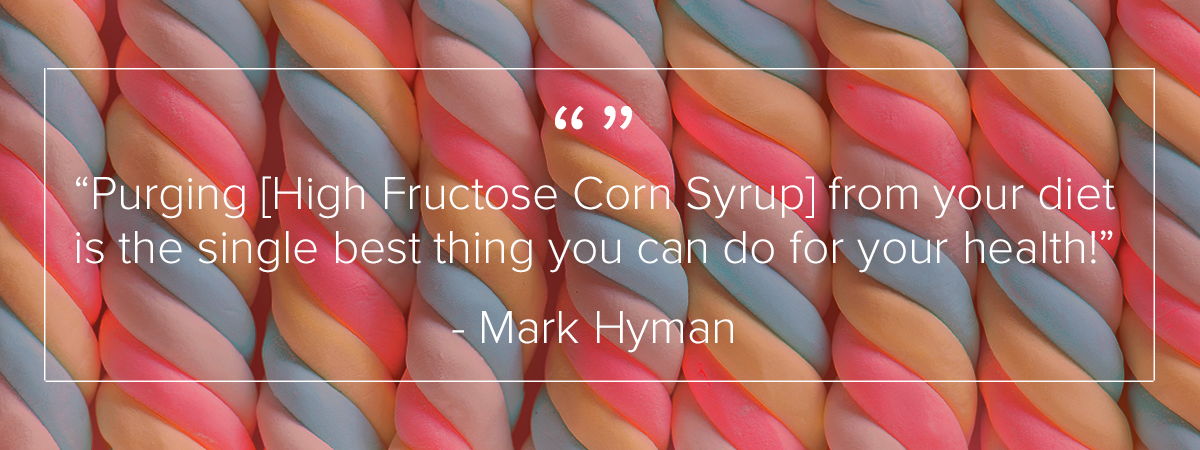 "9 twisting sugar candies are arranged in a line going left to right. The candies are standing vertical. There are three strands of candy twisting to make each candy. The colors of the twists alternate between white, pink, blue, and yellow. Above the image is a quote by Mark Hyman which reads: ""Purging [High Fructose Corn Syrup] from your diet is the single best thing you can do for your health."""