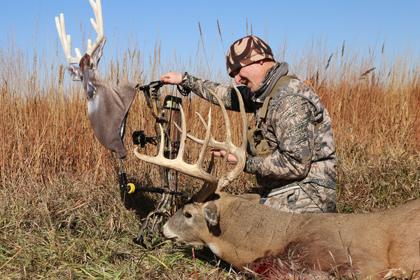 whitetail buck take with a frontal bow shot with heads up decoy