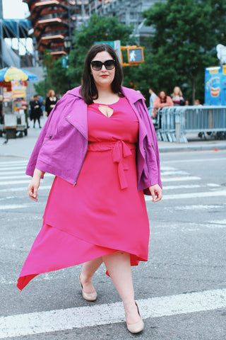 Faith Costa walking across the street in a pink dress