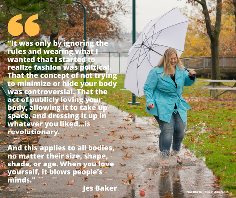 [Image description: A plus-size white woman holds a white umbrella and splashes in a puddle on a park sidewalk covered in autumn leaves. A metal bench, grass, picnic table and trees surround her. She's wearing a blue raincoat, blue jeans and sandals.]