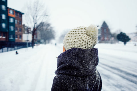 Women wearing white beanie in the snow. This type of hat may be able to be run in the washing machine.
