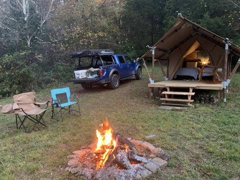 Platform canvas glamping tent beside fire pit and camping chairs.