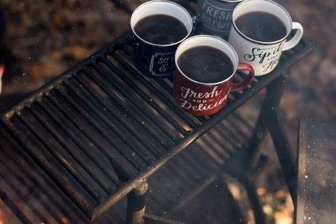 Mugs of coffee beside a campfire in the mist of making a camping cocktail.