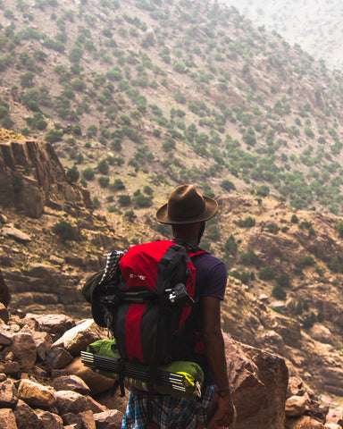 Backpacker hiking in a red rock mountainous area.
