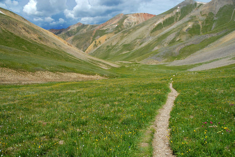 Colorado trail in grassy valley within the Rocky Mountains.