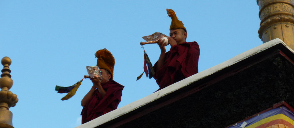 Buddhist monks blowing horns in India on a clear blue day.