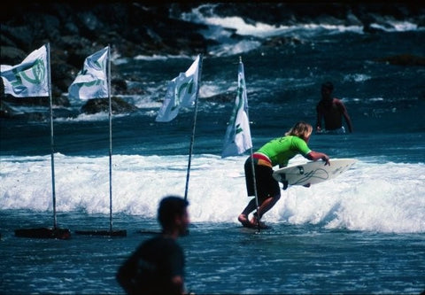 International competitor - surfer entering the water wearing a green Panama Surf lycra t-shirt at the 1994 ASP PANAMA SURF - KOOL Surf World Tour at Isla Grande, Colon in Panama.
