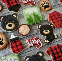 Batch of Cookies from Brooke at CookiesbyBrooke.com with iced cookies decorated as bears plaid onesies pine trees and bear paws