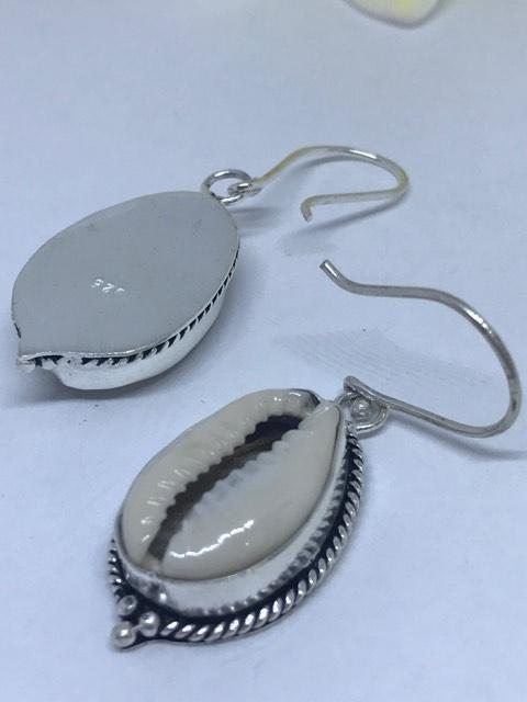 Ocean Girl Earrings with natural white cowrie shells encased in sterling silver