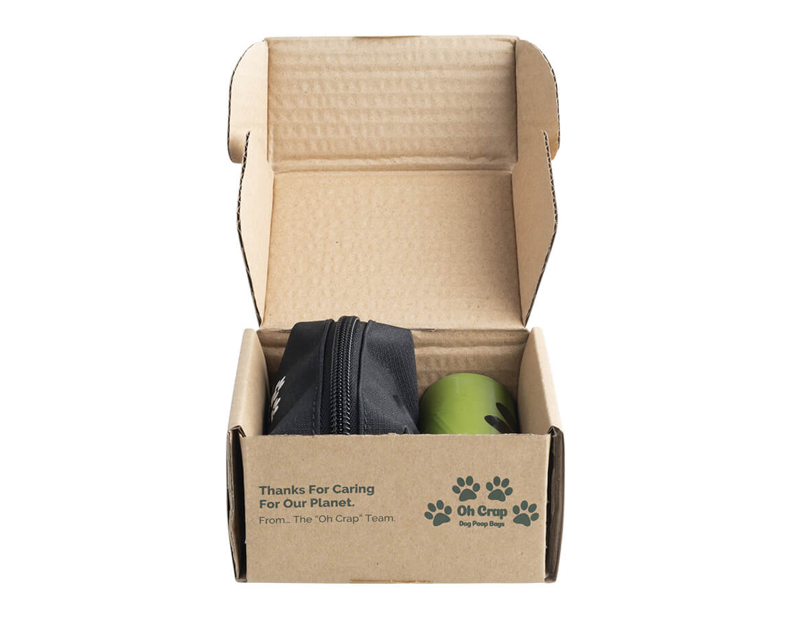The front of the Oh Crap Non Plastic Biodegradable Compostable Dog Poop Bags 1 Month Pack box open with bags & holder inside